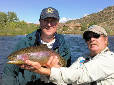 Capt. Mark Nesbit holding up a beautiful rainbow trout for a customer on a San Juan River NM fly fishing trip.